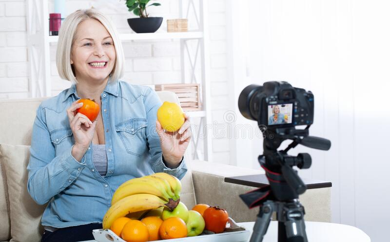 Happy woman blogger shows fruits to the camera at home stock images