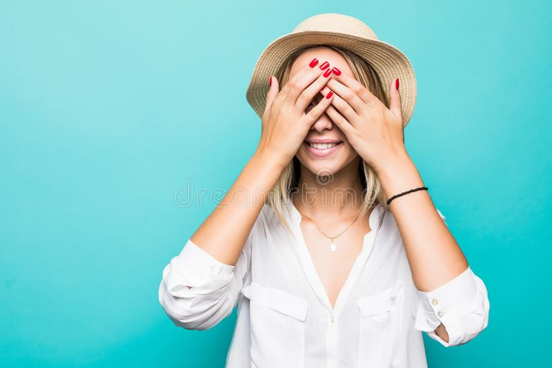 Happy woman with blonde hair closing eyes with hand going to see surprise and smiling in anticipation for something wonderful on b. Happy woman closing eyes with royalty free stock photos