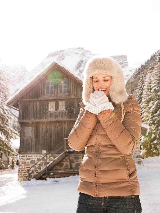 Happy woman blowing warm breath on hands near mountain house. Christmas season in relaxed style of contemporary countryside living. Happy young woman blowing royalty free stock photography