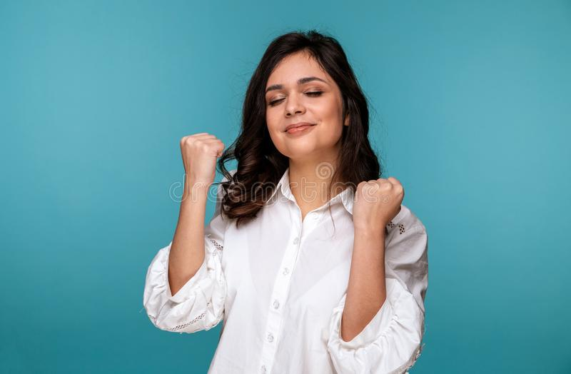 Happy woman on a blue background looking exited. stock photography