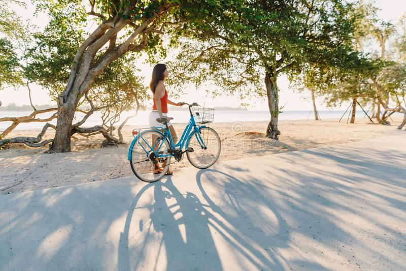 Happy young woman on blue bicycle near ocean in tropical island stock images