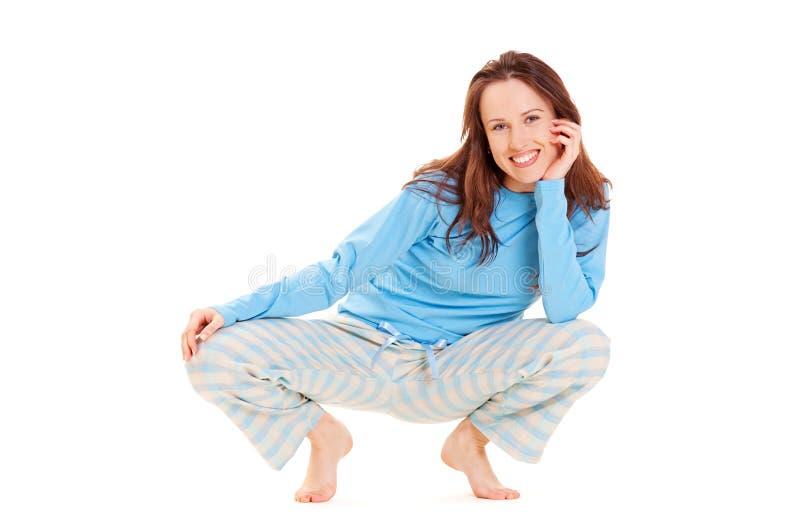Happy woman in blue pyjamas stock photography