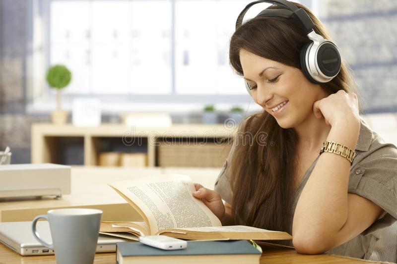 Happy woman with book and headphones royalty free stock image