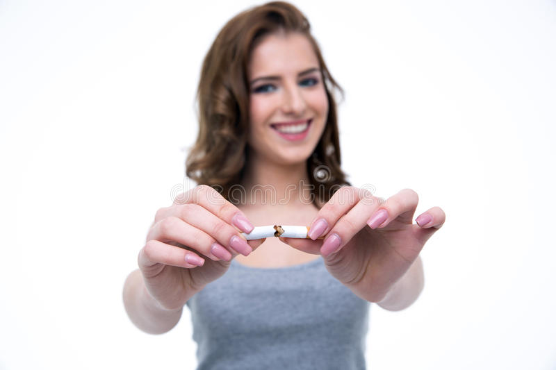 Happy woman breaking cigarette. And no smoking concept. Focus on cigarette royalty free stock photography