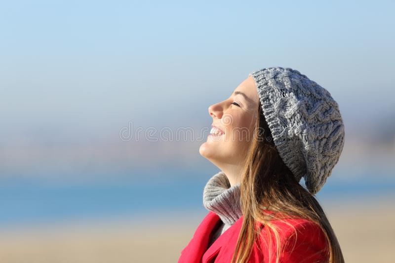 Happy woman breathing deeply fresh air on the beach in winter royalty free stock photo