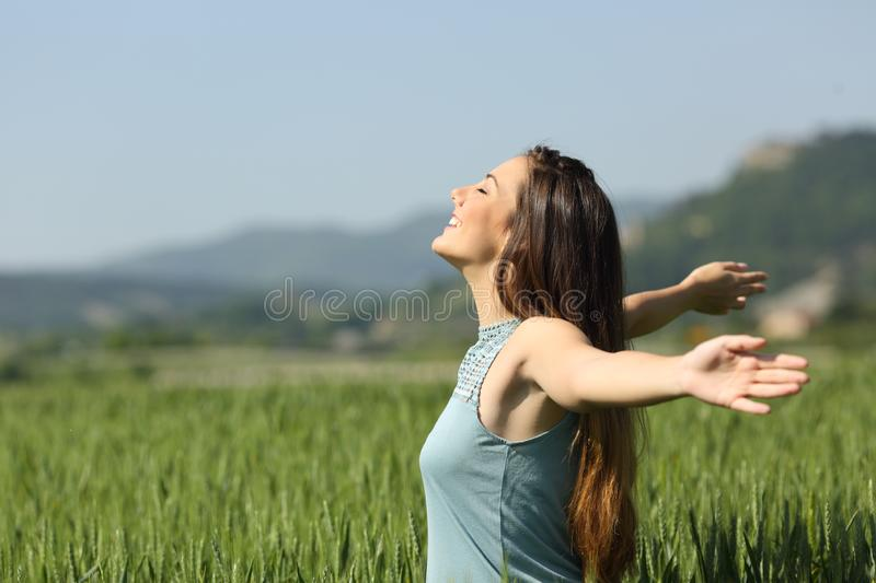 Happy woman breathing deeply fresh air in a field royalty free stock image