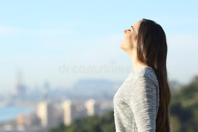 Happy woman breathing fresh air with a city in the background royalty free stock photo