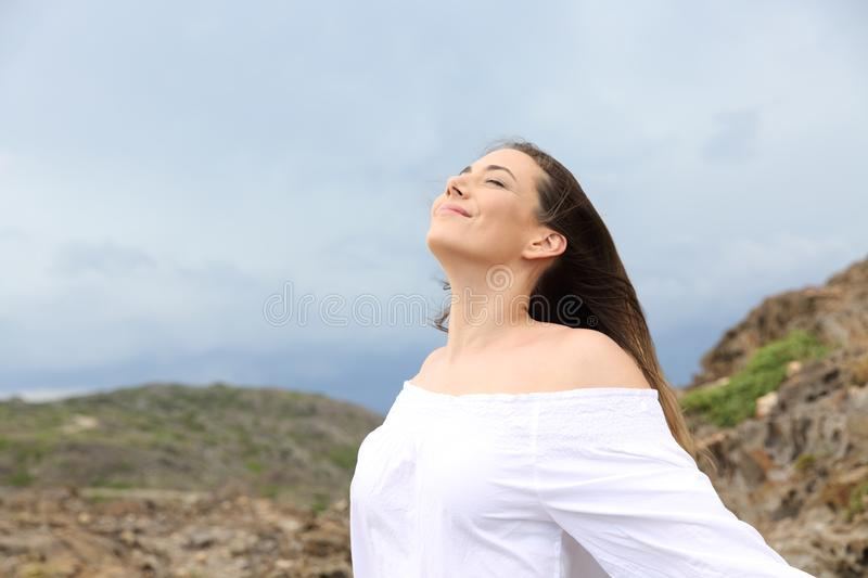 Woman breathing with a storm in the background. Happy woman breathing fresh air with a storm in the background royalty free stock photos
