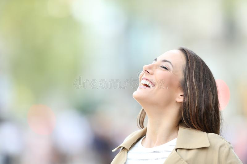 Happy woman breathing fresh air in the street stock photos