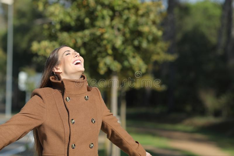 Happy woman is breathing fresh air in winter in a park royalty free stock photos