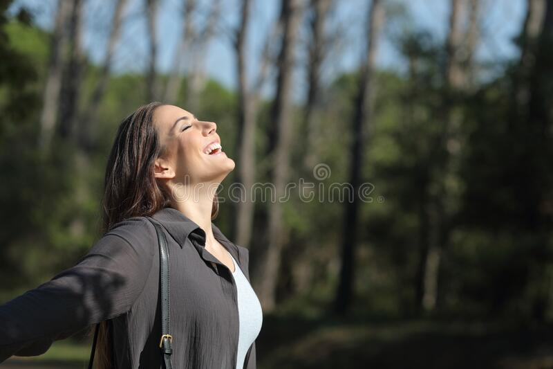 Happy woman breaths fresh air in a park royalty free stock photo