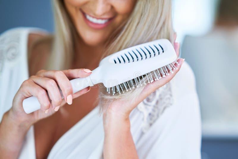 Happy woman brushing hair in bathroom. Adult woman brushing her hair in bathroom royalty free stock photo