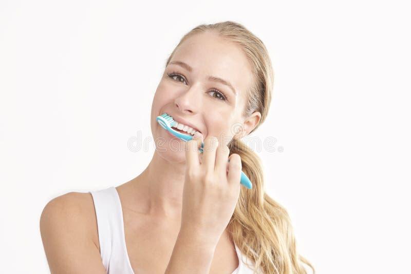 Happy woman brushing her teeth stock photos