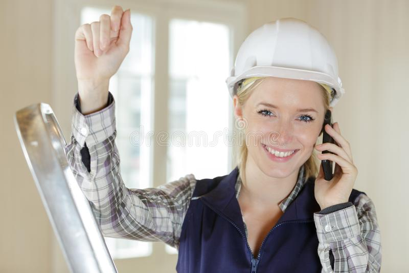 Happy woman builder on phone stock photography