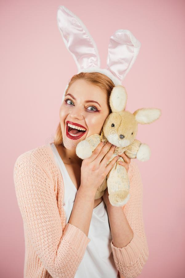 Happy woman in bunny ears with toy. Spring holiday. Girl with hare toy. Woman in rabbit bunny ears. Happy easter. Egg royalty free stock photo