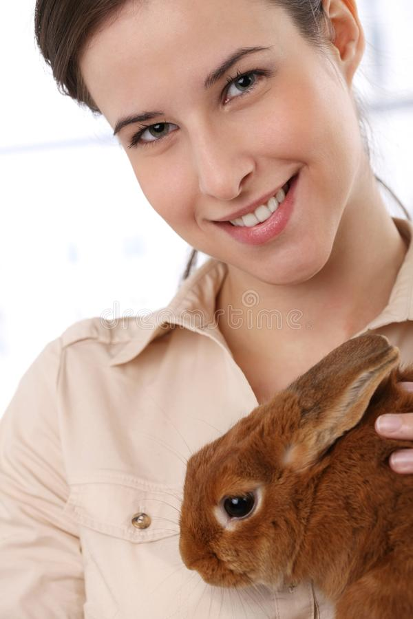 Happy woman with bunny pet. Portrait of happy woman smiling at camera, holding cute bunny pet stock photography