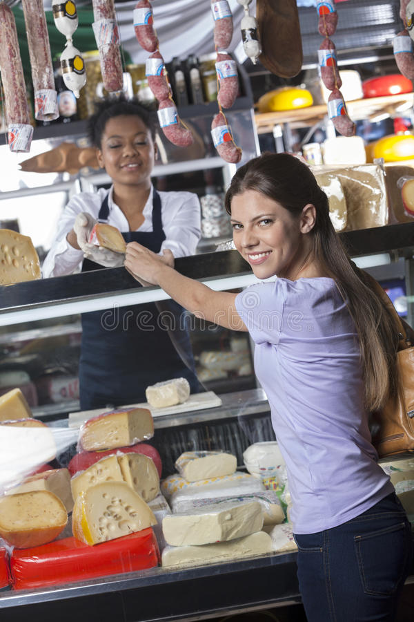 Happy Woman Buying Cheese From Worker At Shop. Portrait of happy young women buying cheese from worker at shop stock photo