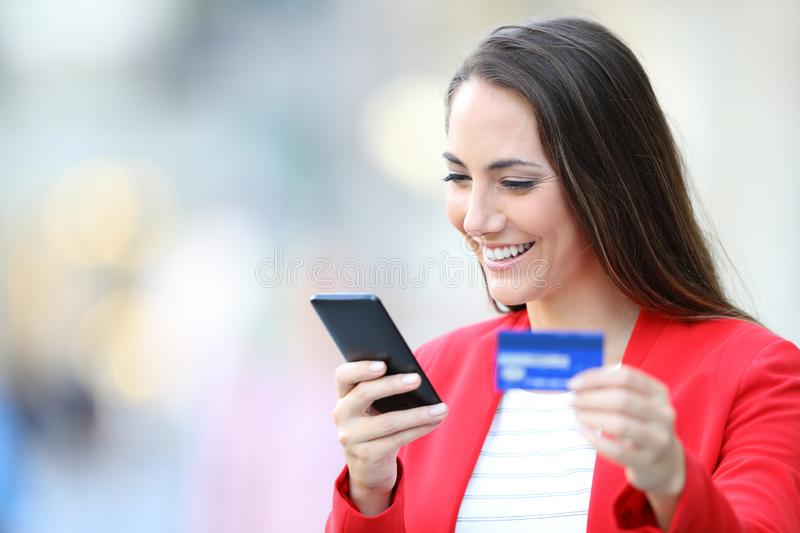 Happy woman buying on line with phone and credit card stock photos