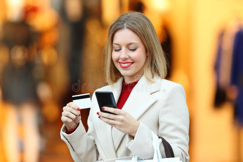 Happy woman buying online with credit card in winter. Happy woman buying online with credit card and smart phone in the street of a commercial centre in winter stock image