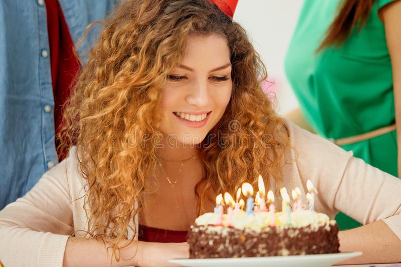 Happy woman with candles on birthday cake at party. Holidays, celebration and people concept - close up of happy redhead woman with candles burning on birthday stock photography