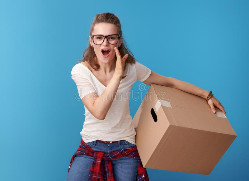Happy woman with cardboard box telling exciting news on blue royalty free stock photography