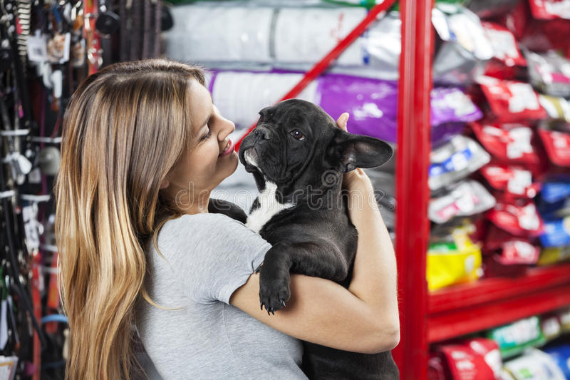 Happy Woman Carrying French Bulldog At Store stock photography