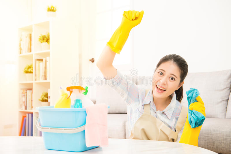 Happy woman celebrate finished cleaning. Happy woman hand up to celebrate finished the house cleaning. Housework concept. mixed race asian chinese model stock images