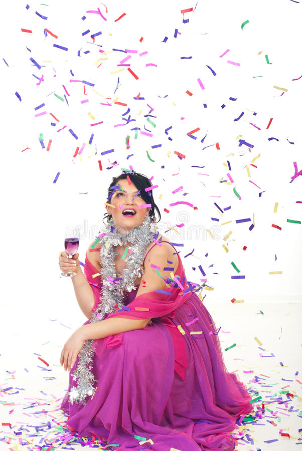 Happy woman celebrate new year party. With champagne and looking up surprised at falling confetti over her while sitting down on floor stock photos