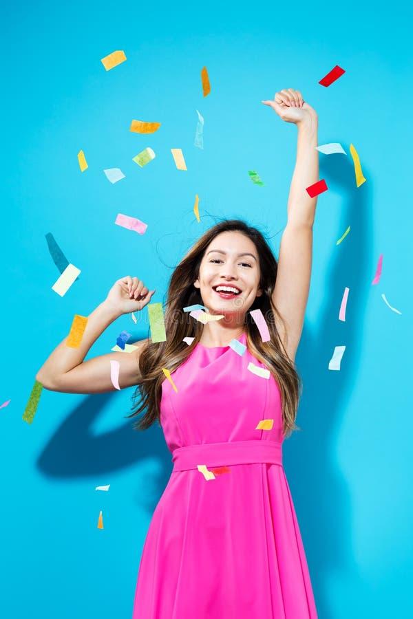 Happy woman celebrating with confetti stock image