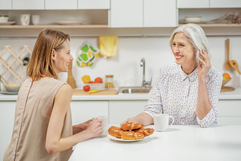 Happy woman chatting with her mature mom royalty free stock images