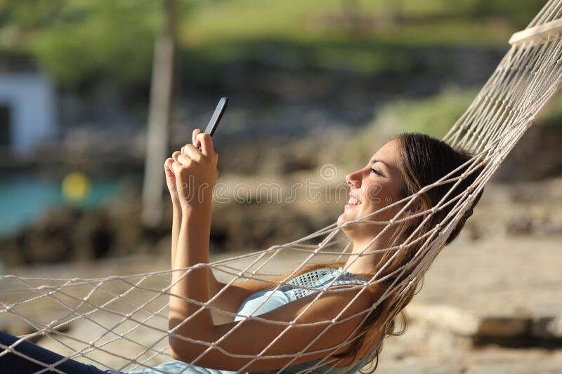 Happy woman checking phone on a hammock on the beach stock photo