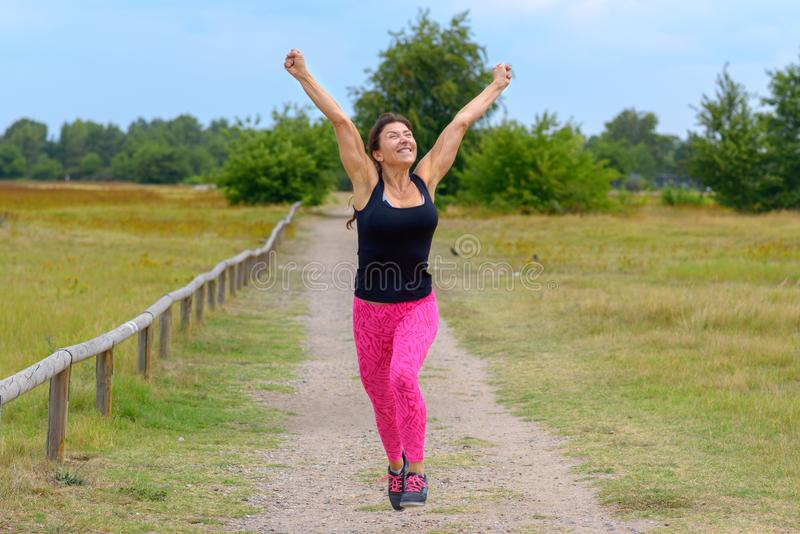 Happy woman cheering and celebrating after working out jogging. Happy fit middle aged woman cheering and celebrating as she walks along a rural lane after stock photography