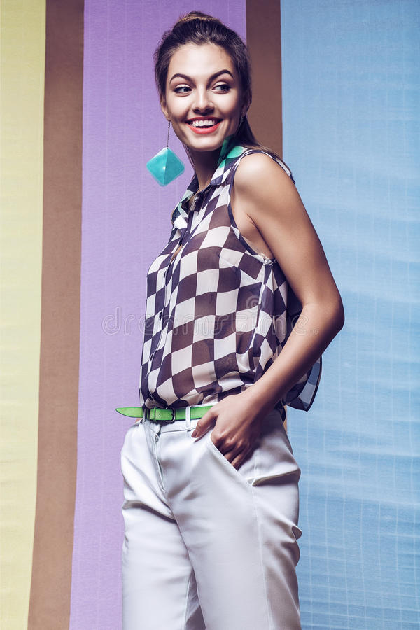 Happy woman in chess shirt, white shorts and aqua earrings royalty free stock photos