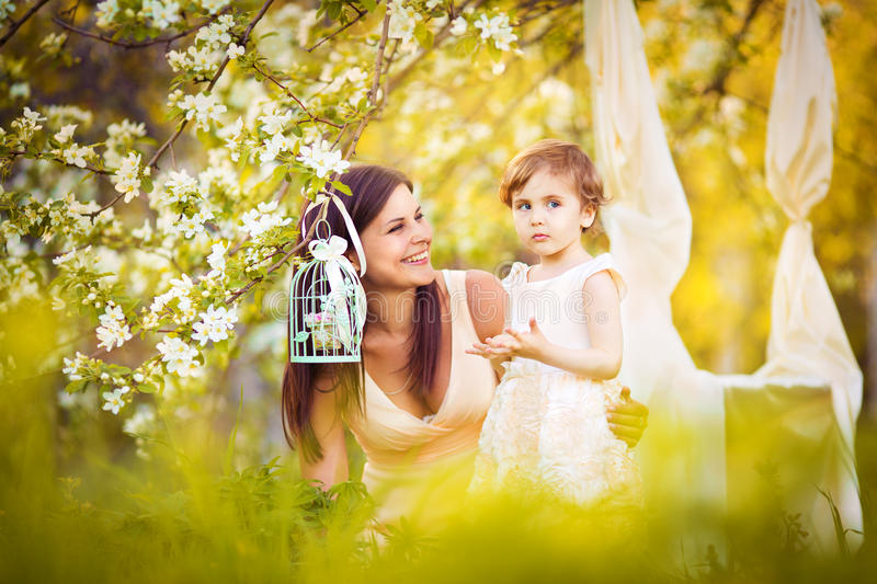 Happy woman and child in the blooming spring garden.Child kissi royalty free stock images