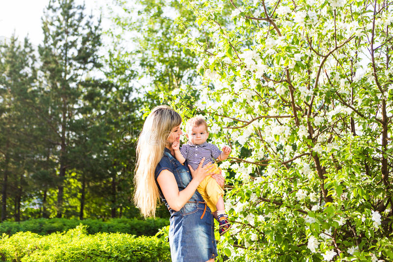 Happy woman and child in the blooming spring garden. Mothers day holiday concept stock images