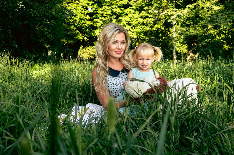 Happy woman and child in the blooming spring garden.Mothers day holiday or womans day concept stock image