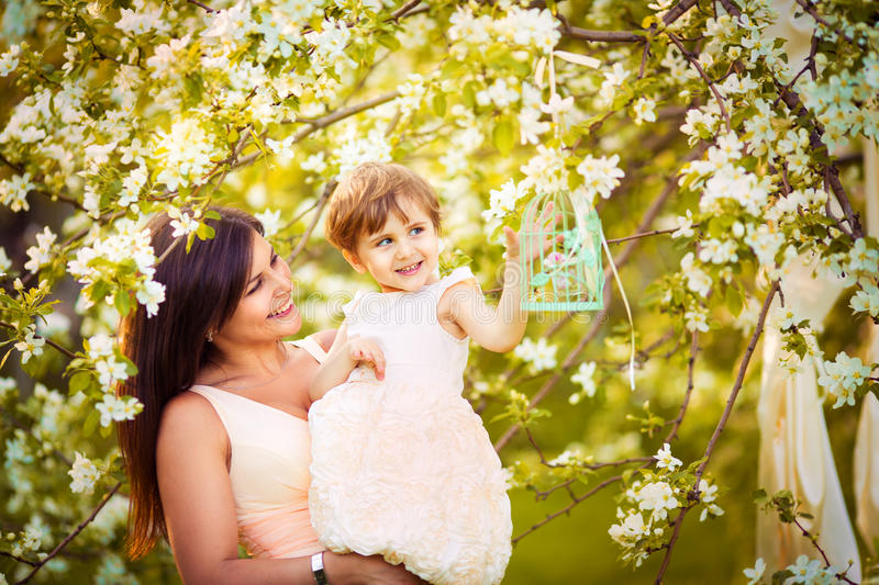 Happy woman and child in the blooming spring garden.Mothers day royalty free stock photography