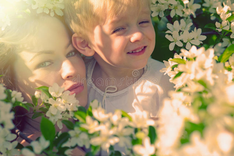 Happy woman and child in the blooming spring garden stock photo