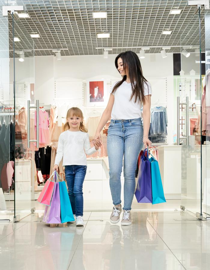 Happy woman and child holding shopping bags in store. stock photography