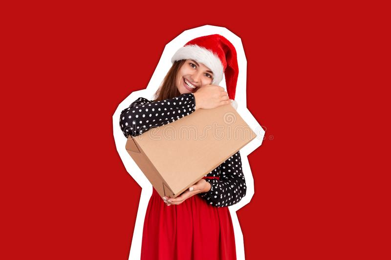 Happy woman in chistmas hat hugs a gift wrapped in recycled paper. Magazine collage style with trendy color background. holidays. Concept stock photos