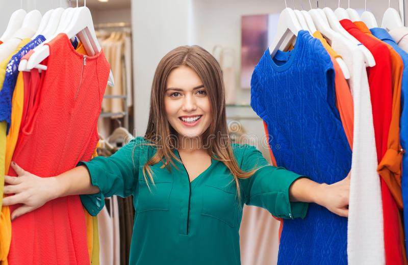 Happy woman choosing clothes at clothing store. Fashion, shopping and people concept - happy woman choosing clothes in clothing store stock photography