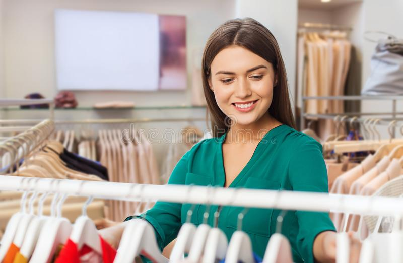 Happy woman choosing clothes at clothing store. Fashion, shopping and people concept - happy woman choosing clothes in clothing store stock images