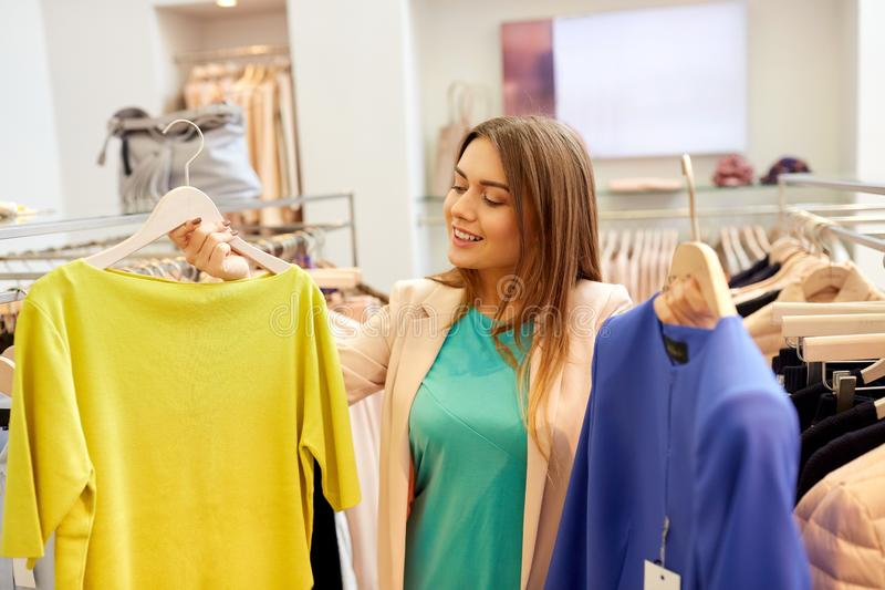 Happy woman choosing clothes at clothing store. Shopping, fashion, sale and people concept - happy young woman choosing clothes in mall or clothing store royalty free stock photos