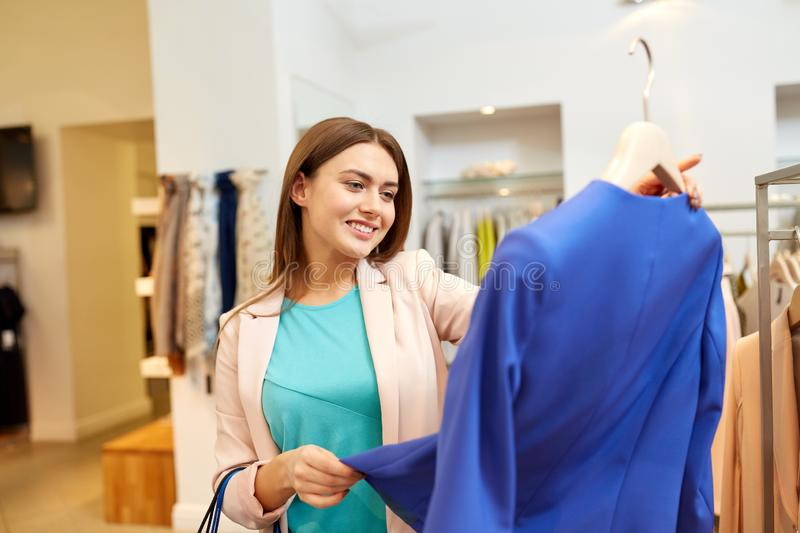 Happy woman choosing clothes at clothing store. Shopping, fashion, sale and people concept - happy young woman choosing clothes in mall or clothing store royalty free stock images