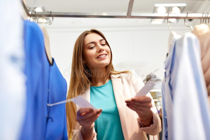 Happy woman choosing clothes at clothing store. Shopping, fashion, sale and people concept - happy young woman choosing clothes in mall or clothing store and stock photography