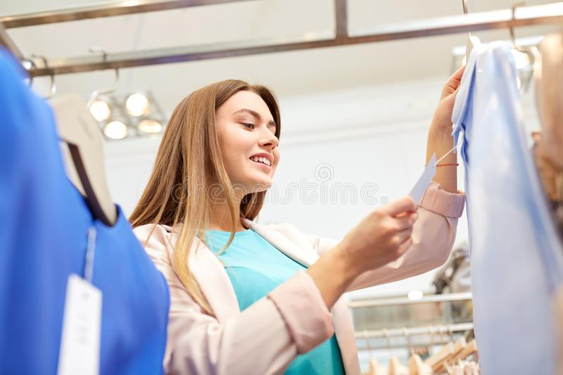 Happy woman choosing clothes at clothing store. Shopping, fashion, sale and people concept - happy young woman choosing clothes in mall or clothing store and stock images