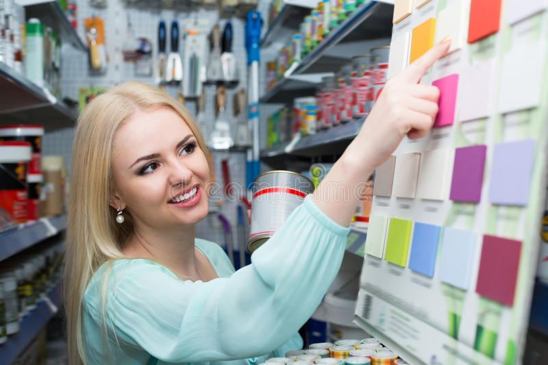 Happy woman choosing decorating paint. In household section of supermarket stock images