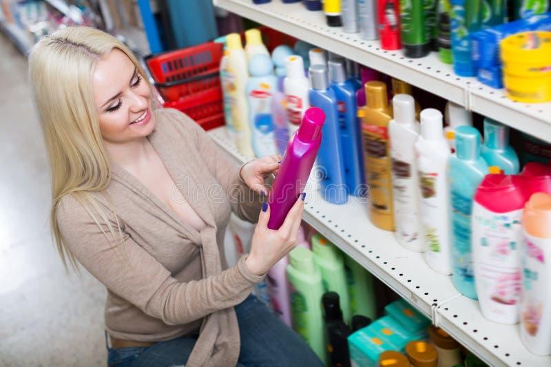 Happy woman choosing hair conditioner royalty free stock photos