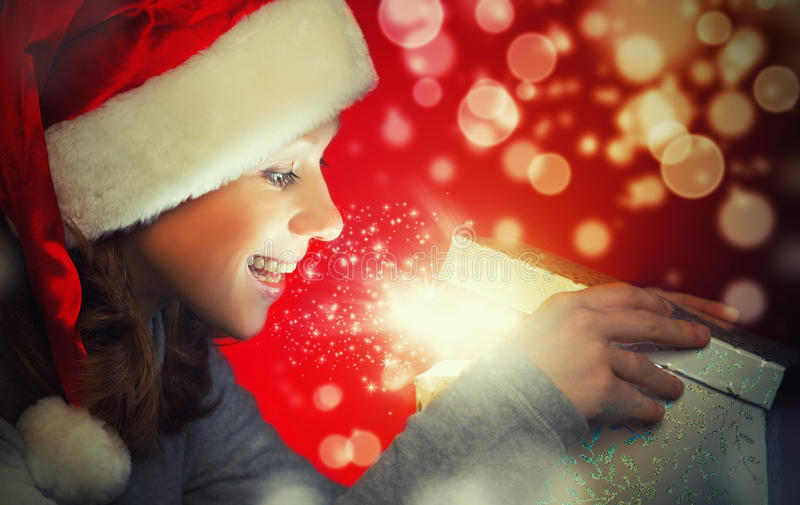 Happy woman in a Christmas cap opens the magic box. Gift stock images