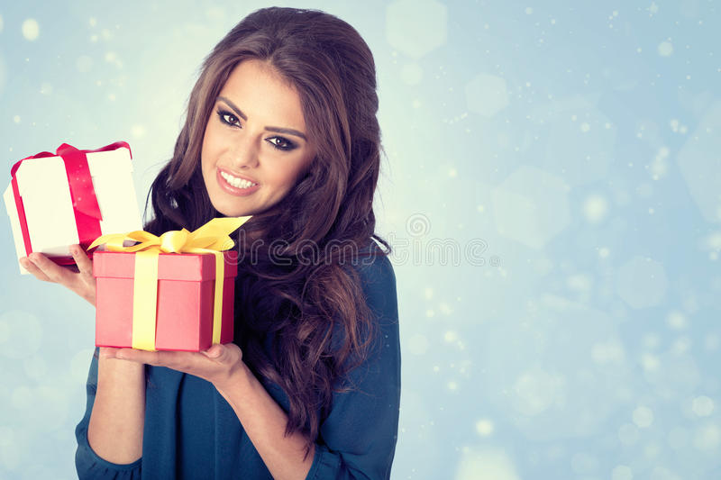 Happy woman with christmas gifts. blue background. royalty free stock image